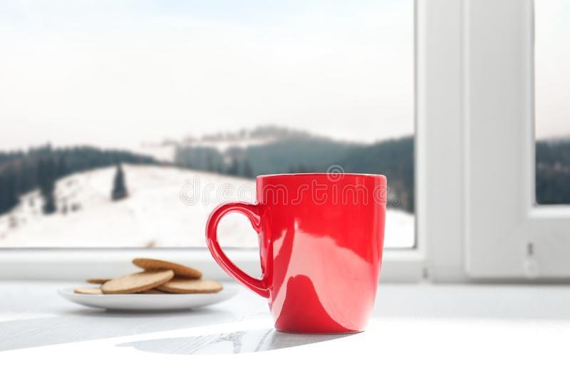 hot-drink-cookies-near-window-view-winter-mountain-landscape-152877428.jpg